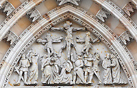 Crufixion high relief carved in stone within a Gothic arch on the central gate of the Main Portal or hlavni portal of St Vitus Cathedral, a Gothic Roman catholic cathedral founded 1344, within Prague Castle, Prague, Czech Republic. The relief work was completed by O Spaniel according to the plans of V H Brunner. The cathedral's full name is the St Vitus, St Wenceslas and St Adalbert cathedral and is the largest church in the Czech Republic. The historic centre of Prague was declared a UNESCO World Heritage Site in 1992. Picture by Manuel Cohen