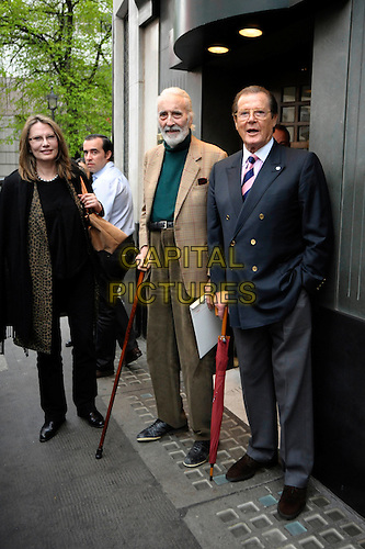 MAUD ADAMS, CHRISTOPHER LEE & SIR ROGER MOORE .Having a Bond reunion lunch at The Ivy Club this afternoon, London, England..April 26th, 2010.full length blue suit jacket grey gray trousers umbrella cane beige green brown black leopard print scarf.CAP/DYL.©Dylan/Capital Pictures.