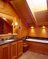 The wood-clad bathroom has a black marble basin and bath surround
