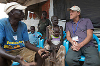 South Sudan, Juba: Friday 14 March 2019 <br /> British actor Jerome Flynn visits POC1 (Protection of Civilians) in the Central Equiatoria district of Juba to see the hard work that World Vision aid workers are doing to help some of the 1.7million internally displaced people of South Sudan. There are three POC's in Juba, POC1 is home to approximately 7,000 IDPs. Pictured: Jerome speaks with Steven Banguot 67 (left), his sister Nyamer Chuol 65 (centre) with their granddaughter Nyadhil (on lap) who live in POC1.