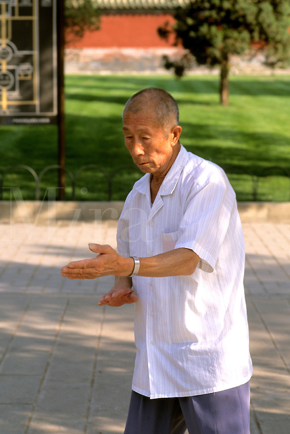 Elderly Chinese man practicing tai chi exercise in a local park in Beijing China
