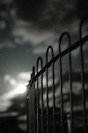 An iron railing with clouds blurred