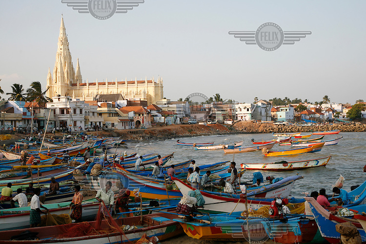 Fishermen in fishing boats tend their nets near a church in Kanyakumari (formerly known as Cape Comorin) on the southernmost tip of India. Although Kanyakumari is an important pilgrimage site for Hindus, a large percentage of its population is Christian.