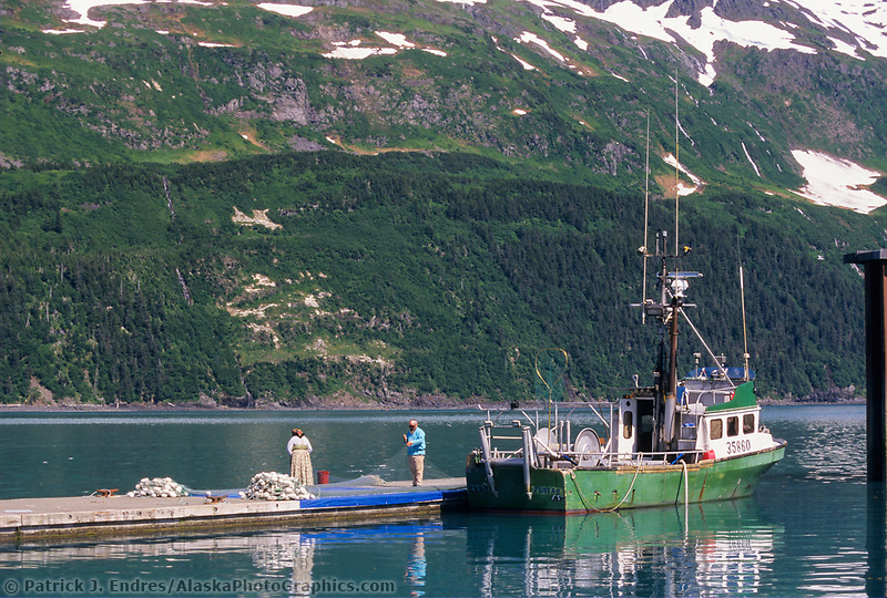 Russian family mends drift net for commercial salmon fishing with a bowpicker, Whittier, Alaska