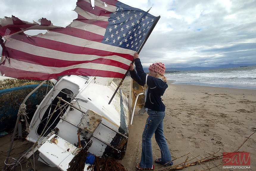 Lauren Klammer,9, restores a tattered flag she found broken off a beached boat Sunday. Several boats fell victim to the recent rough weather in Southern California. The wind ripped at least five boats from their moorings offshore Santa Barbara and sent them crashing onto East Beach. Forecasters said the rain will continue this week with downpours likely.