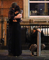 Pictured: A woman rests against a bollard in the early hours of Saturday, 17 December, 2016<br />