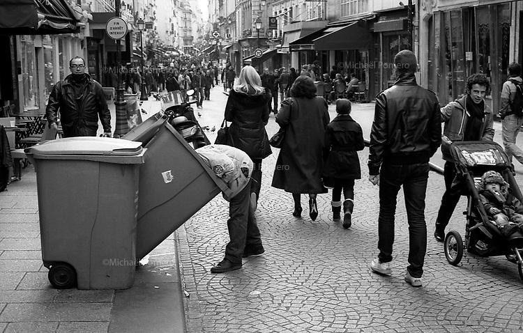 Paris (&icirc;le de france)<br /> <br /> Sans abris en train de fouiller dans une poubelle en pleine rue.<br /> <br /> Homeless rummaging in the garbage in the street.
