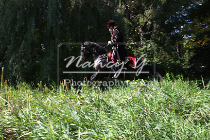A Russian Cossack riding a horse jumping over a creek