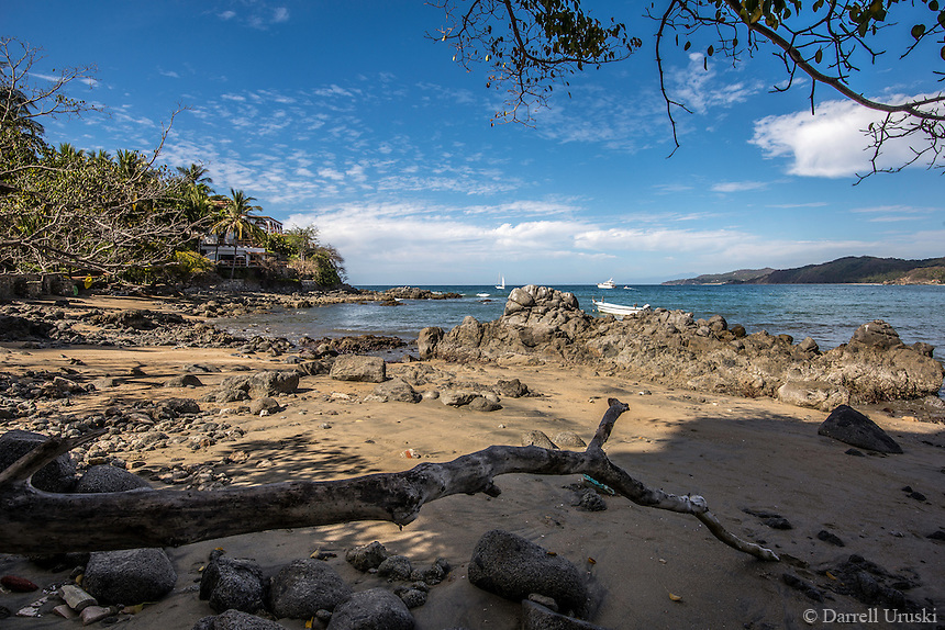 Fine Art Landscape Photograph of the ocean shoreline in Sayulita Mexico. <br /> The sandy beach, the tree branches, and the unique rock formations helped to frame  this picturesque tropical scene.