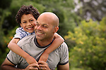 Mixed race father playing with son