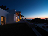 As the sun sets over the Mediterranean outdoor lights illuminate the portico at one end of the villa