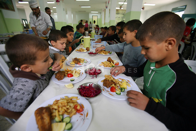 Palestinian orphan children eat lunch at the Hebron's orphan house, in the West Bank city of Hebron 24 May 2012.  Hebron's orphan house  contain about 100 orphan children from ages 6 to 18 years old, and oversees some of orphans in their houses. Photo by Mamoun Wazwaz