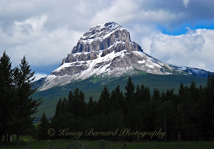 Summer morning in the Canadian Rockies snow capped Crowsnest Mountain stretches into the cloudy skies.