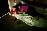 Meredith Soble, left, and her son Dale Soble, 2, try to sleep on the floor of a multipurpose room at Stockton's Shelter for the Homeless, July 18, 2012. With some of the highest rates of unemployment and home foreclosures in the country, Stockton, the largest US city to declare bankruptcy, is grappling with large numbers of homeless.