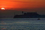 The sunrises over Alcatraz Island as fisherman head out to sea in a small boat.