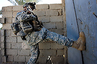 A US soldier from second platoon, Alfa company, 1st battalion, 506th, 101st airborne division tries to kick in a steel door while executing OPERATION TEEN WOLF, a raid in a neighborhood of western Ramadi with the purpose of searching for insurgency weapons, gather intel and meet with the civilian population, in the city of Ramadi, Iraq on Tuesday January 03 2006. during the raid four suspected Sunni insurgents were held  by the US military for further interrogations.