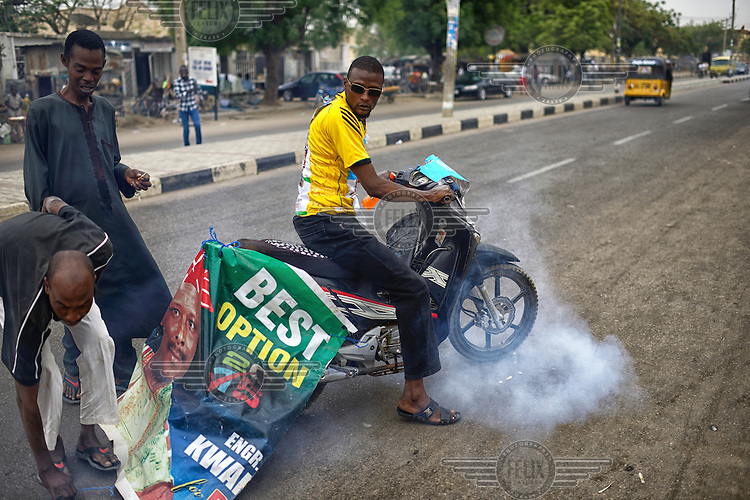Jubilant youths tie a campaign poster to the back of a motorbike as people come onto the streets of Kano to celebrate the victory of Muhammadu Buhari, leader of the APC (All Progressives Congress Party), in the 2015 Nigerian Presidential elections.