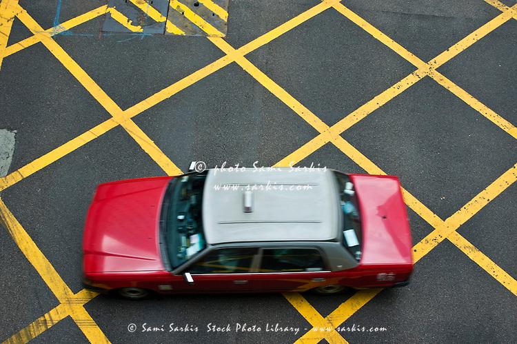 Red taxi cab driving over yellow lines, Hong Kong Island, Hong Kong, China.