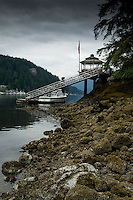 Boat moored at private jetty with gazebo and flag staff. Deep Cove Bay with clouds above the mountains over Mount Seymour provincial park. Deep Cove, Burrard Inlet, Vancouver, British Columbia, Canada.