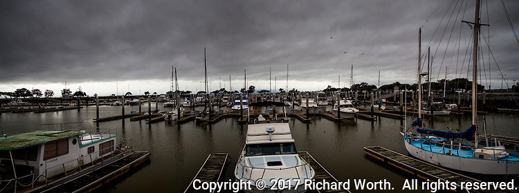 Fishing and sail boats are moored at San Leandro Marina under heavy clouds overhead while on the horizon a break appears with a band of lighter clouds in the distance.