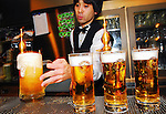 A barman serves glasses of Sapporo beer at Sapporo Beer Station, a beer garden in Tokyo, Japan
