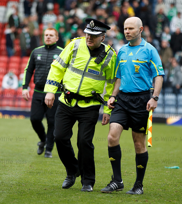 The match officials are escorted off the pitch by police