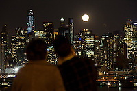 People take pictures of the moon rise along the skyline of Middle Manhattan while it is seen from Weehawken in New Jersey March 27, 2013. Photo by Eduardo Munoz Alvarez / VIEWpress.
