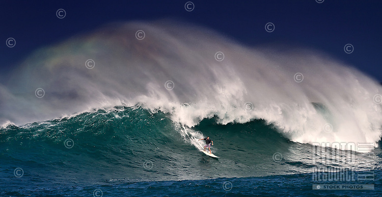 Surfer at Oahu's Sunset Beach with a beautiful rainbow in the spray of the wave.