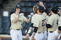 D.J. Poteet (4) of the Wake Forest Demon Deacons is greeted by his teammates after hitting his first career collegiate home run against the Gardner-Webb Runnin' Bulldogs at David F. Couch Ballpark on February 18, 2018 in  Winston-Salem, North Carolina.  The Demon Deacons defeated the Runnin' Bulldogs 8-4 in game one of a double-header.  (Brian Westerholt/Four Seam Images)