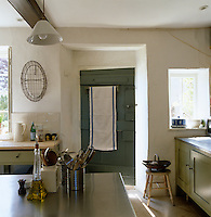 A rustic wooden door opens from the kitchen into the garden