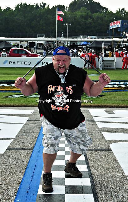 World's Strongest Redneck (Steve McGranahan) bends steel bar over his head at the start of the 2009 NASCAR Truck race Memphis Motorsports Park