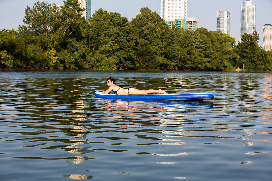 A Woman Enjoying Stand Up Paddle Boarding (SUP) on Lady Bird Town Lake Austin on beautiful summer's day. Austin, Texas.