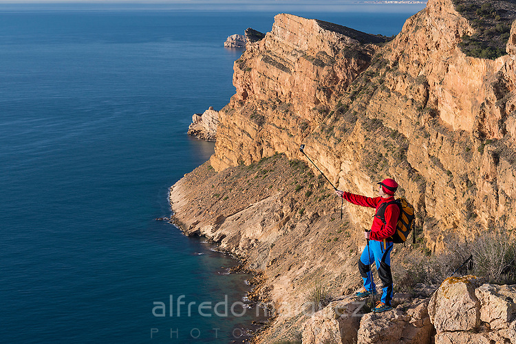 Hiker takes Gopro video over the Mediterranean sea from Sierra Helada natural park cliff, Benidorm, Alicante province, Spain