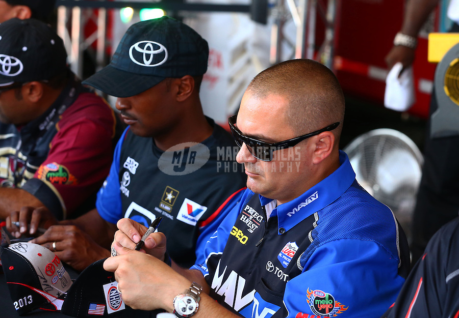 Jun. 1, 2013; Englishtown, NJ, USA: NHRA top fuel dragster driver Brandon Bernstein (right) signs autographs with Antron Brown during qualifying for the Summer Nationals at Raceway Park. Mandatory Credit: Mark J. Rebilas-