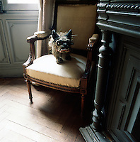 A model of a dog sits on a carved wooden armchair set in the corner of a room next to fireplace.