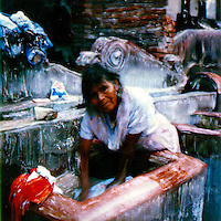 The mother washes the family clothes at the public washing tubs at the village park.<br />