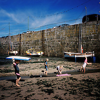 Children play near boats in the harbour in Mousehole, Cornwall.
