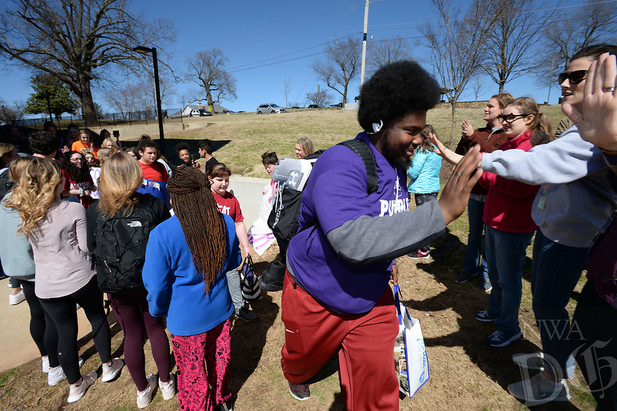 NWA Democrat-Gazette/ANDY SHUPE<br /> Ke Shawn Chism, a junior at Fayetteville High School gets high-fives Friday, March 15, 2019, from parents and teachers as he boards a bus bound for the Special Olympics state basketball tournament in Russellville. Chism is a standout player on the Bulldog team that won a regional tournament earlier this semester.