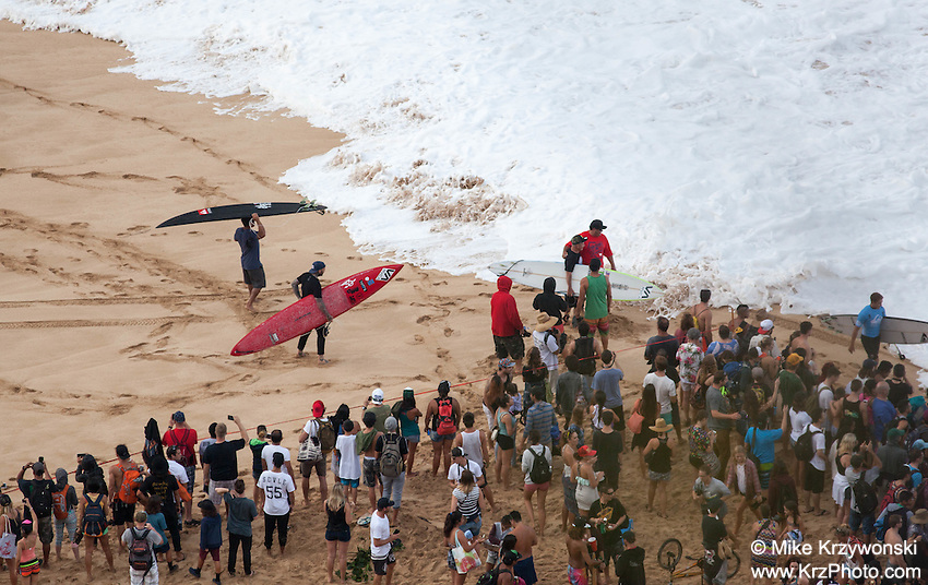 Crowd of spectators watching competetors at the shore just before paddling out at the 2016 Big Wave Eddie Aikau Contest, Waimea Bay, North Shore, Oahu