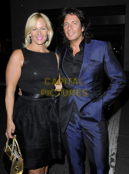 JACKIE LLEWELYN-BOWEN & LAURENCE LLEWELYN-BOWEN.Nicky Haslam's book launch party, Westbury Hotel, London, England. .April 21st, 2010 .half 3/4 length black sleeveless dress blue suit married husband wife hand in pocket.CAP/CAN.©Can Nguyen/Capital Pictures.