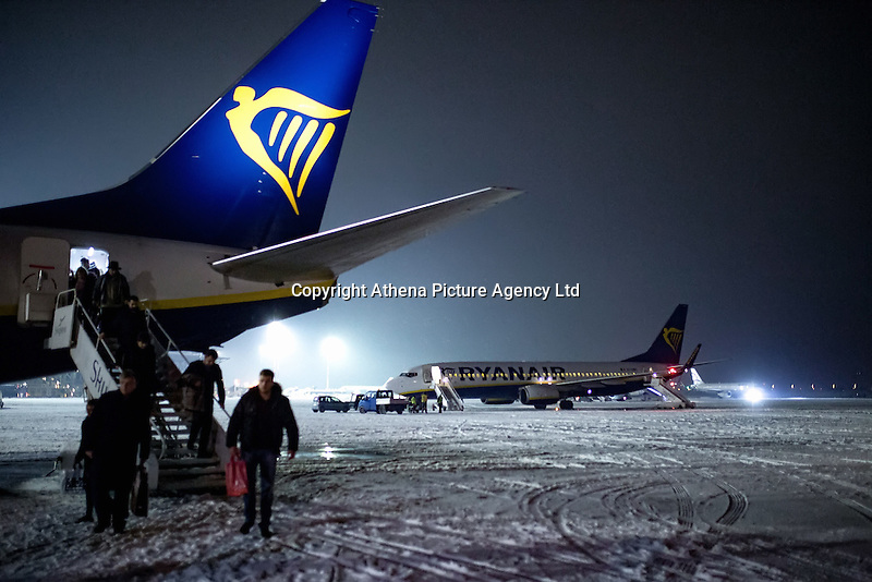 Pictured: Passengers disembark a RyanAir flight on the snow covered Macedonia Airport in Salonica, northern Greece in the early hours of the morning. Thursday 12 January 2017<br />