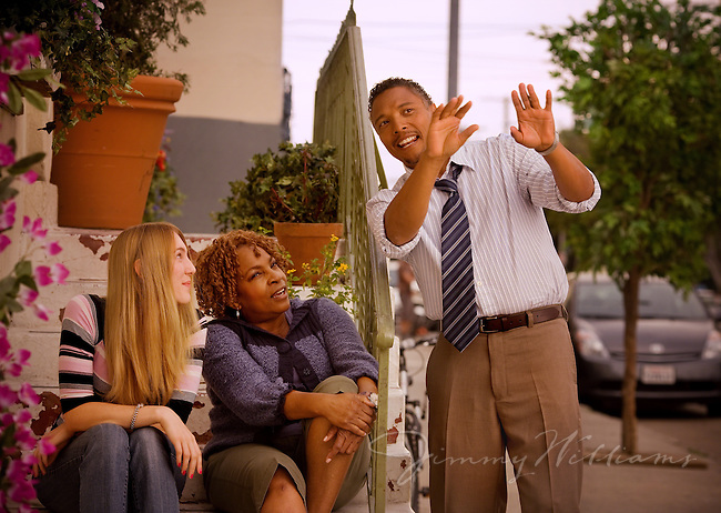 A man talks with his two neighbors on the front steps of his row house in Los Angeles, California