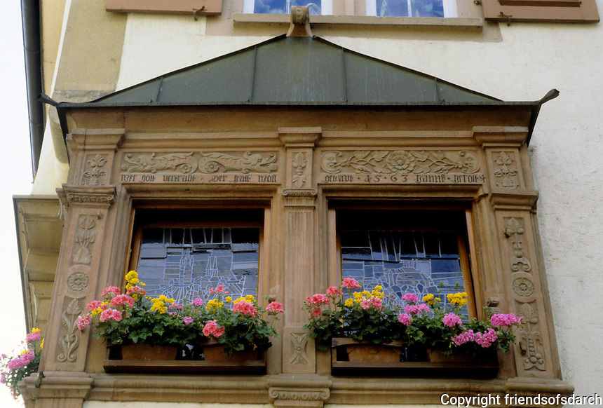 Bad Wimpfen: Carved wood window frames; flowers. Note decorative glass in windows.