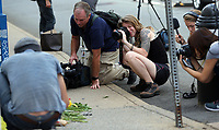 Media surround a small make-shift memorial of flowers on 4th Street SE Sunday near where a woman was killed and several other injured after a Unite the Right rally in Charlottesville, Va. Photo/Andrew Shurtleff