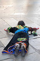Tibetan Buddhist woman prostrating on the Barkhor pilgrim circuit around the Jokhang Temple, Lhasa, Tibet.