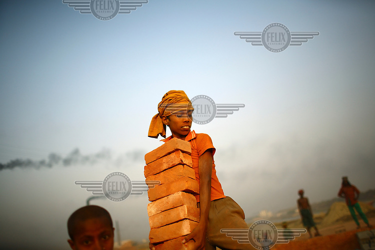 A young boy carries a load of large bricks in a brick making factory. For each thousand bricks they move the labourers are paid the equivalent of about GBP 0.56.