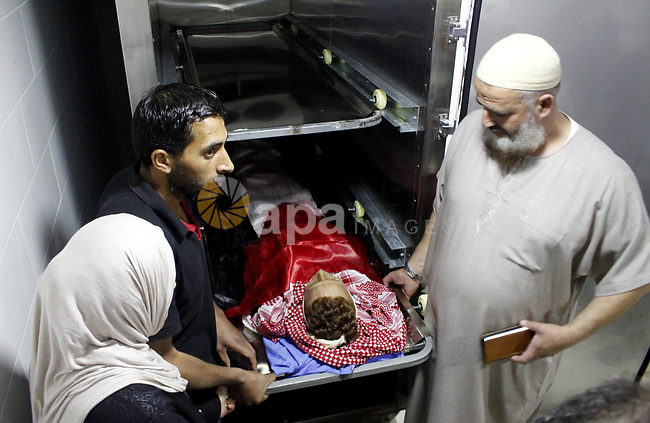 Mourners carry the body of Palestinian Naseem Al-Roumi, 14, was shot dead by Israeli forces for allegedly attempting to carry out a stabbing attack on August and Israeli army kept his body withheld since that, during his funeral in the West Bank village of Al-Eizariya, near east of Jerusalem, on September 21, 2019. Photo by Mosab Shawer