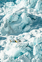 Helicopter is dwarfed by size of massive blocks of ice of Main Icefall on Franz Josef Glacier, Westland National Park, West Coast, UNESCO World Heritage, New Zealand, NZ