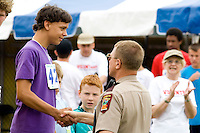Police officer congratulating winning athlete. Special Olympics U of M Bierman Athletic Complex. Minneapolis Minnesota USA