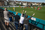 Home supporters celebrating their team's first goal at the Mersey Travel Arena, home to Marine Football Club (in white), as they played host to Ilkeston FC in a Northern Premier League premier division match. The match was won by the home side by 3 goals to 1 and was watched by a crowd of 398. Marine are baed in Crosby, Merseyside and have played at Rossett Park (now the Mersey Travel Arena)  since 1903, the club having been formed in 1894.